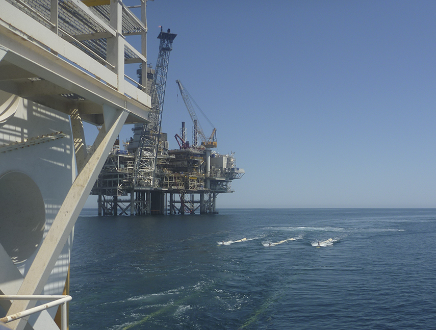 Photograph showing the operational source phase post OBC operations over the AGC oilfield with an oil platform in the background